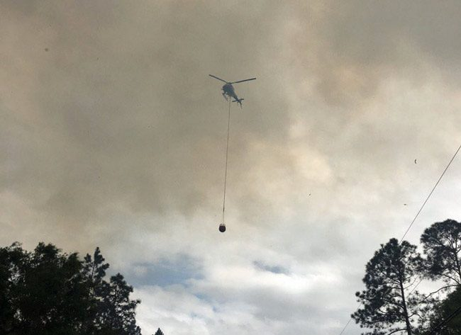 Flagler County Fire Flight, the emergency helicopter, was dumping water on the b;laze all afternoon. (Forest Service)