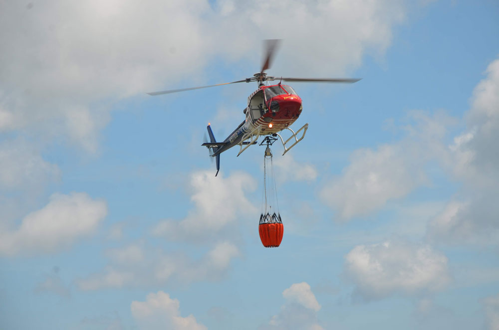 Flagler County Fire Flight, the emergency helicopter, and its water bucket. Emergency personnel hope to use the helicopter as little as possible as the fire season ramps up, with a burn ban intended to minimize emergencies. (© FlaglerLive)