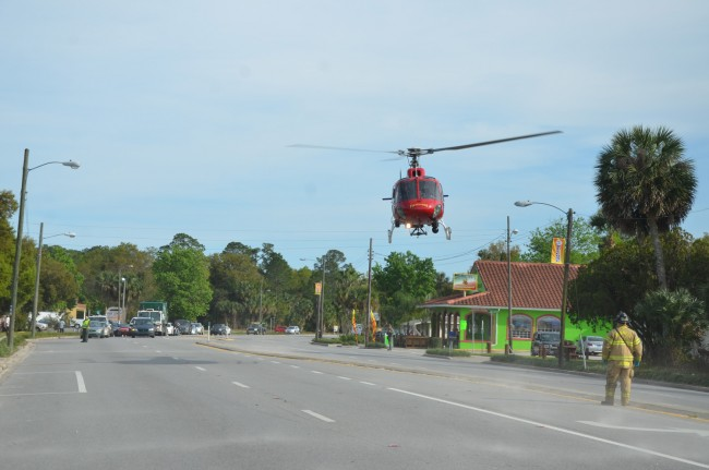 'Action Jackson,' more officially known as Jackson, a firefighter-paramedic with Flagler County Fire Rescue, guided Fire Flight off U.S. 1 in Downtown Bunnell Thursday afternoon as part of the evacuation of two trauma patients. A second patient was transported to Daytona Beach's Halifax hospital by ground. (© FlaglerLive)