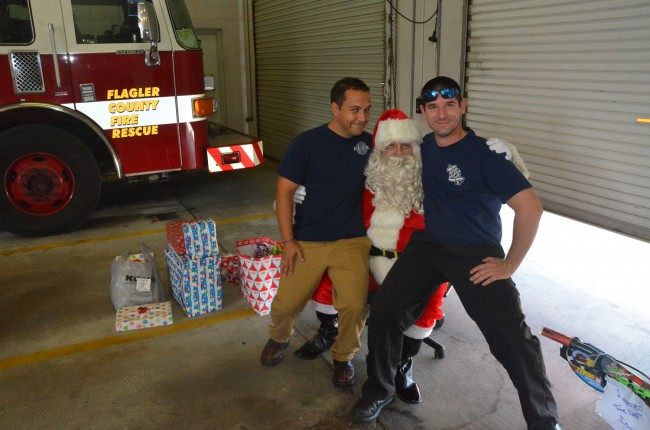 Firefighters need their Santa too: Lt. Armando Castaneda, left, and Fierfighter-Paramedic Matt Braasch sit on knees that in other times and places belong to Palm Coast firefighter Patrick Juliano. Click on the image for larger view. (© FlaglerLive)