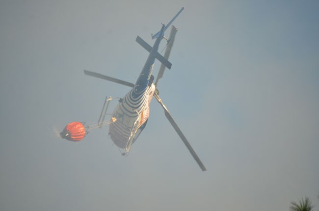 Fire Flight flew in the thick of the smoke to drop its water loads. (c FlaglerLive)