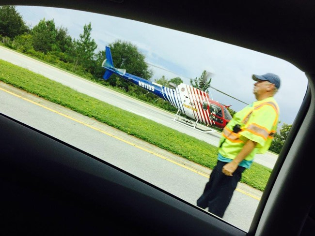 A reader took that  perfect frame of Flagler County Fire Flight, the emergency helicopter, when it made a landing on Belle Terre Parkway Monday afternoon during the emergency started by the single-vehicle car wreck involving Palm Coast resident Peter Slusarz. That's Steve Garnes, captain of the Palm Coast Fire Police, to the right. (© FlaglerLive)