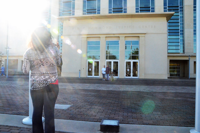 Michele Villa and Dawn Wilcox posed, along with their grandson Ethan,  with the marriage license they had just filled out, as their daughter Ariana Butkiewicz took  a picture in front of the Flagler County courthouse this morning. Villa and Wilcox were the third same-sex couple to get a license today in Flagler. (© FlaglerLive)