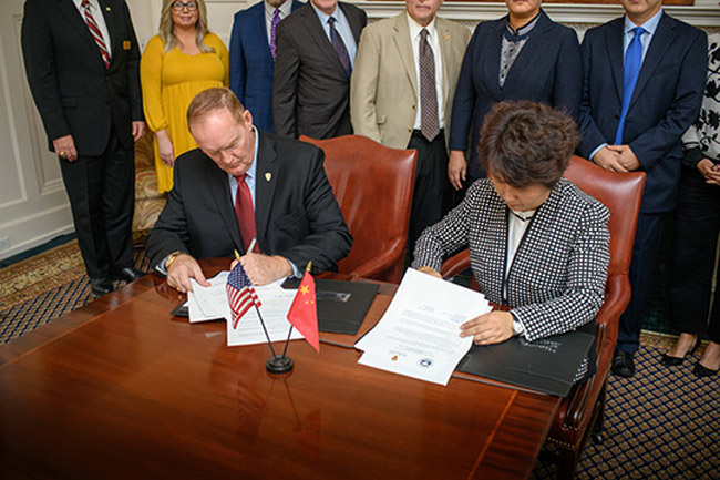 Flagler College President Joseph G. Joyner signs the agreement with CFAU Vice President LI Hongmei. (Flagler College)