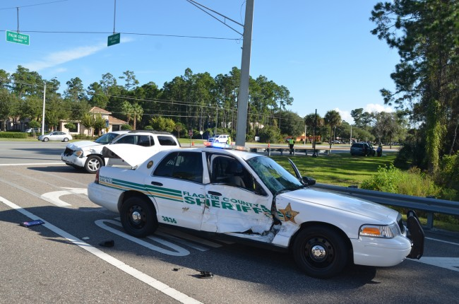 Flagler County Sjheriff's deputy James Gore was struck on the passenger side by the GMC SUV at Palm Coast Parkway and Pine Lakes Parkway Thursday morning. Click on the image for larger view. (© FlaglerLive)
