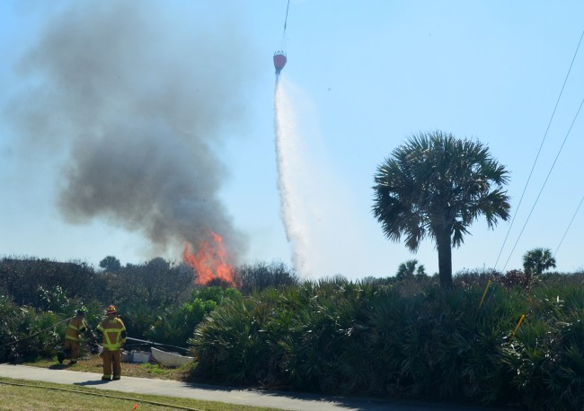 Flagler County Fire Flight dumped dozens of water loads on the fire after it jumped A1A and began moving toward Island Estates, flaring up on several occasions. Click on the image for larger view. (© FlaglerLive)