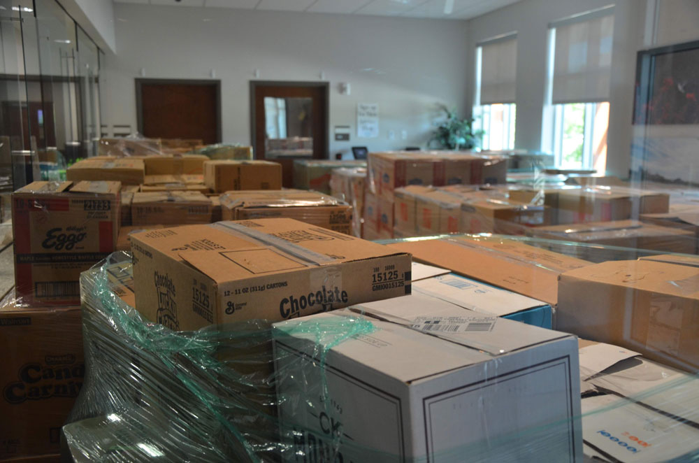 At Palm Coast City Hall, the entire customer service department's public room has been transformed into a storage zone for food packages awaiting distribution during Feed Palm Coast Saturday, when the city will distribute some 3,000 packages and Parkview Church is expected to distribute 2,000. (© FlaglerLive)