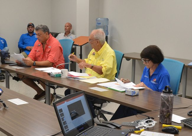 Florence Fruehan, in the orange shirt, at an East Flagler Mosquito Control District meeting in 2017, with board members Julius Kwiatkowski and Barbara Sgroi. (c FlaglerLive)