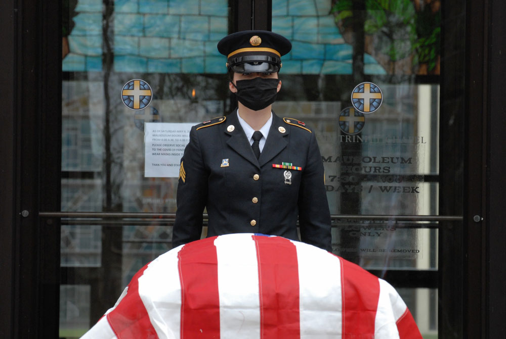 Sgt. Nikole Clark, a member of the New York National Guard Military Funeral Honors Team, stands posted at the casket of U.S. Army Air Force Cpl. Raymond Kegler during his funeral in Lackawanna, New York, May 14. Clark wore a face mask as part of precautions being used during military funerals to prevent the spread of COVID-19. (Army National Guard Photo by Capt. Avery Schneider)