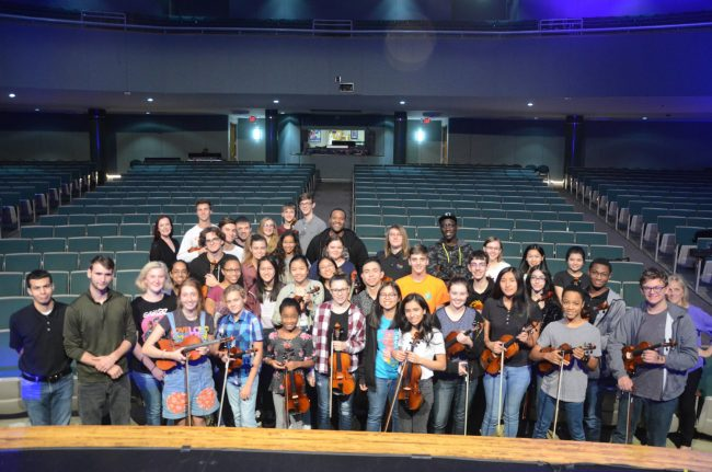 Black Violin duo members Kev Marcus and Wil B, in the rear row, gave members of the Flagler Youth Orchestra's Harmony ensemble a special hour-long master class Monday before Black Violin's 7:30 p.m. performance at the Flagler Auditorium. Marcus invited several of the students on stage to improvise and told them all to follow their passion if they want to end up like him--doing what he loves most nights of the year on stage. Monda's was Black Violin's last performance of the year. (© FlaglerLive)