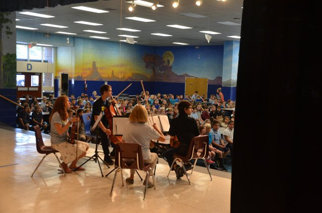 The Flagler Youth Orchestra Quartet was in performance at Old Kings Elementary before third and fourth graders, part of its annual recruiting tour through district schools. The quartet also performed today at Bunnell and Rymfire elementaries, and did so on Tuesday at Belle Terre Elementary and Wadsworth Elementary. Students are introduced to the free, district-supported after-school program and introduced to the various instruments they could play. Some 320 students have registered so far, with two weeks left in the enrollment period, which ends with an open house at Indian Trails Elementary on Sept. 6. (© FlaglerLive)