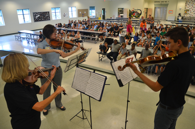 Sue Cryan, left, led a Flagler Youth Orchestra trio during Thursday's recruiting tour in a stop at Bunnell Elementary. She was accompanied by Maggie Snively and Daniel Masbad. (© FlaglerLive)