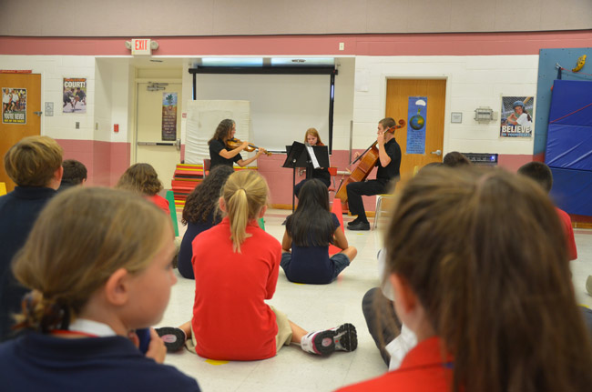 Fifth graders at Wadsworth Elementary heard a Flagler Youth Orchestra trio--Caren Umbarger, Mary Thopson and Austin Smith--play them the sort of music they;d be able to play after a few years in the program. (© FlaglerLive)