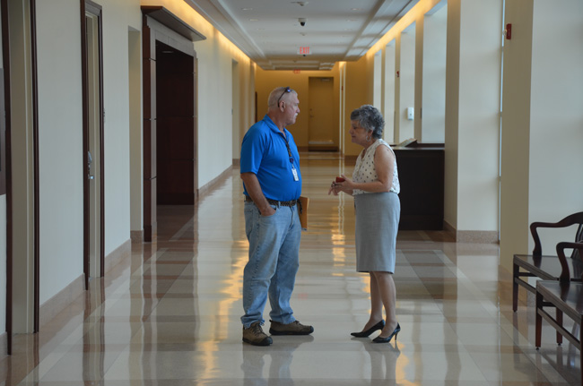 In her element: Clerk of Court Gail Wadsworth, seen here at the courthouse, speaking to Commissioner Frank Meeker, says the timing isn;t right for her to 'abandon' ongoing projects and run for a legislative seat. Meeker, too, is foregoing a run. (© FlaglerLive)