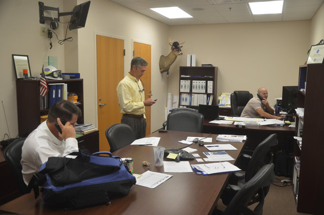 Steve Garten, the Flagler County Emergency Services manager, right, in his office in the aftermath of Hurricane Matthew last year, with County Administrator Craig Coffey, left. Property Appraiser Jay Gardner is standing. (c FlaglerLive)