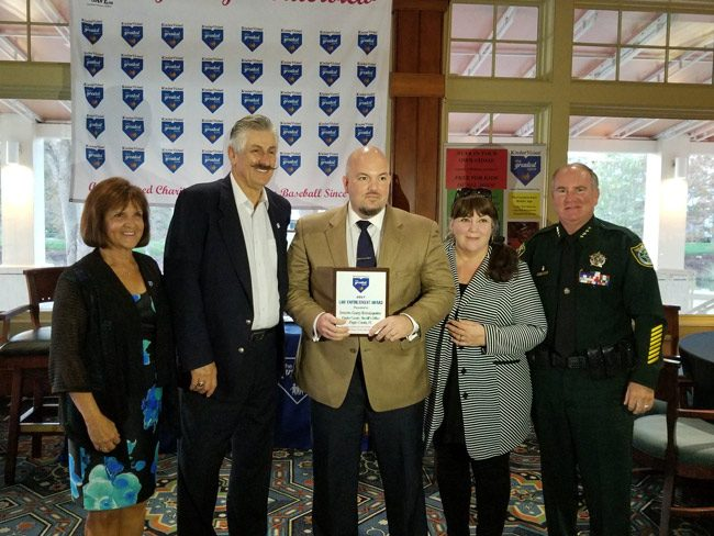 Flagler County Sheriff Detective George Hristakopoulos, center, accepting the Greatest Save award Monday from baseball legend Rollie Fingers, the tallest man in the room. With them were Director Nancy Sebastian, Hristakopoulos's mother, and Sheriff Rick Staly. (FCSO)