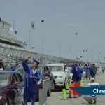 Caps went airborne as Matanzas High School graduates prepared for their victory lap this morning at the Daytona International Speedway. (© FlaglerLive via Flagler Schools)