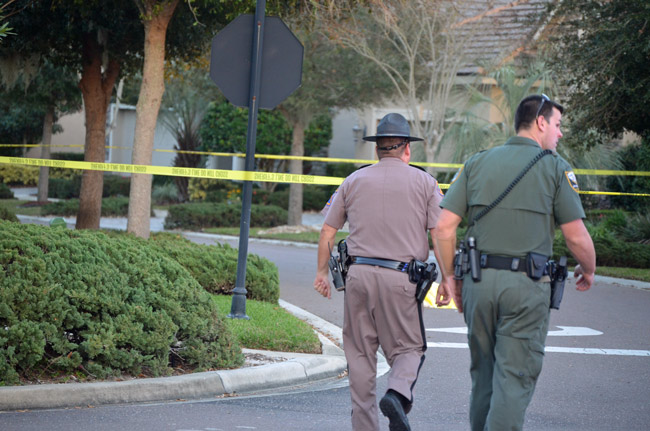 A Florida Highway Patrol investigatopr and a Flagler County Sheriff's deputy were at the scene, awaiting the arrival of a homicide investigator and the medical examiner. Until then, the body of the victim, under a yellow tarp ahead of the two law enforcement officers, could not be moved. (© FlaglerLive)