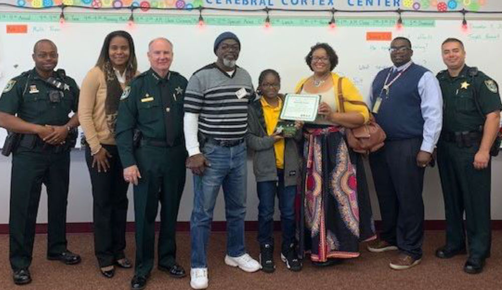Deputy Robin Towns, Rymfire Elementary School Principal Mrs. Moore, Sheriff Rick Staly, D'Zyon Coates with family, Rymfire Elementary School Assistant Principal Mr. Lee, and Commander Phil Reynolds.