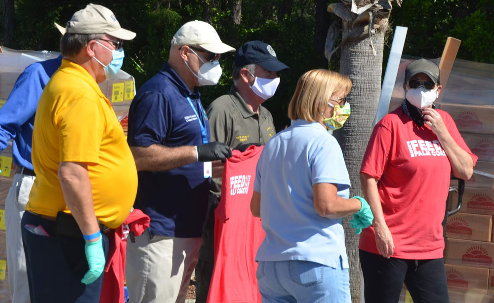 County Commissioner Greg Hansen in the yellow shirt with other local officials at last month's big food distribution in Palm Coast. (© FlaglerLive)