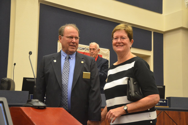 Greg Hansen and his wife Linda Hansen immediately after the swearing in by County Judge Melissa Moore-Stens. Commissioner Charlie Ericksen is in the background. (© FlaglerLive)
