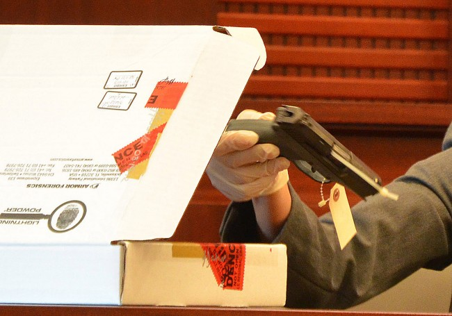The 9mm gun Paul Miller used to murder his neighbor Dana Mulhall in Flagler Beach in March 2012, as Maria Pagan, an FDLE crime analyst, displayed it during the trial that led to Miller's conviction on a second-degree murder charge last month. Click on the image for larger view. (© FlaglerLive)