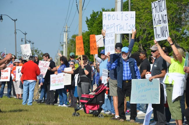 More than 100 people stretched across Palm Coast Parkway on both sides of Boulder Rock Drive this morning between 10 a.m., and noon. Many demonstrators went on to other planned marches in the region, from St. Augustine to Orlando. Click on the image for larger view. (© FlaglerLive)