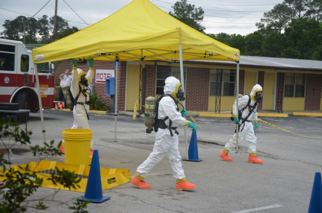 The HazMat team carried a tent to cover a police cruiser that had to be decontaminated, in the parking lot of the Budget Motel. (c FlaglerLive)