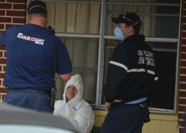 Fire rescue personnel interviewed the motel's cleaning lady, known as Carol, at 1 p.m., outside a room. (c FlaglerLive)