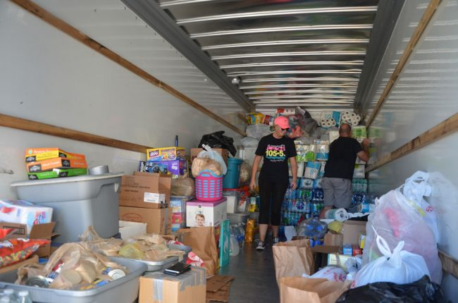 Heather and Scott Reinhardt organizing the 26-foot truck's contents around 9 a.m. today. (c FlaglerLive)