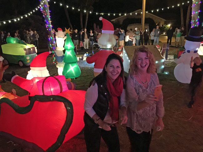 Two of the year's biggest local election winners, Palm Coast Mayor Milissa Holland, left, and School Board member and most-senior elected-official Colleen Conklin, celebrate the lighting of the Christmas display at Conklin's Flagler Beach house, an annual event that drew almost as many people as there were lights. The display is mostly the labor of Chris Conklin, Collen's husband, who estimates it takes about 60 hours to put together. (© FlaglerLive)