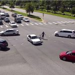 Christopher Holmes, his car stopped in the middle of the intersection, walked around gesturing. It was one amid a series of bizarre and criminal incidents Thursday afternoon. (© FlaglerLive via FCSO video)