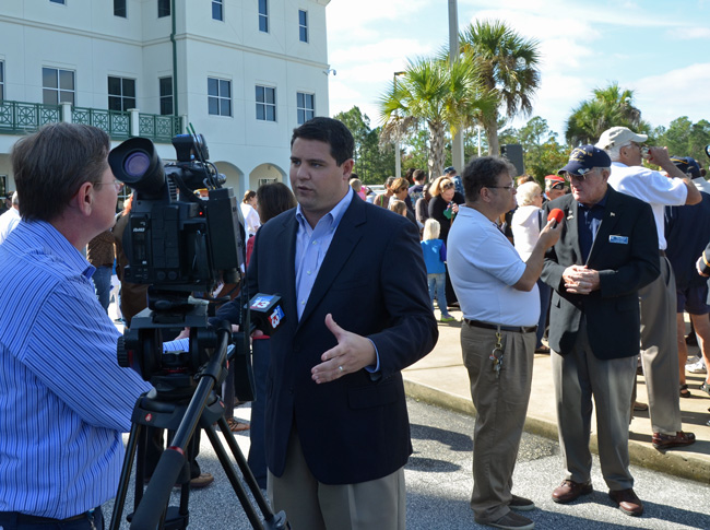 The candidates line up: Travis Hutson, in the foreground, speaks to Channel 13's Jason Wheeler about his intention to run for the Senate, while Flagler REC Chairman Dave Sullivan is interviewed by WNZF's Ron Charles about his intention to run for Hutson's House seat. The scene was shortly after this morning's Veterans Day commemoration in front of the Government Services Building in Bunnell. (© FlaglerLive)