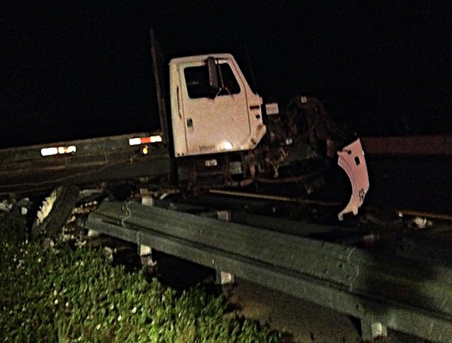 One of the three trucks involved in Wednesday evening's wreck on I-95, on the bridge above State Road 100, had been carried on the flatbed of another truck. It ended up straddling the center guard rail. (John's Towing)