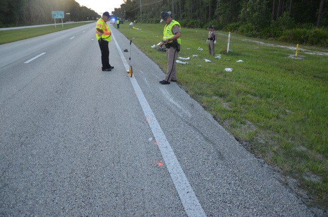 An FHP investigator examined the point of impact on U.S. 1's shoulder, where fresh gashes traced the trajectory of the bike after it was struck. Click on the image for larger view. (© FlaglerLive)