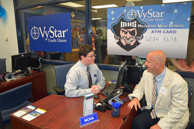 Flagler School Superintendent Jacob Oliva was the Matanzas High School VyStar branch's first customer today, opening a credit union account as student-employee Fred Beyder, a junior, walked him through the process. (© FlaglerLive)