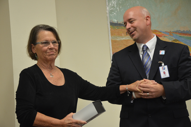 Janet Valentine officially passed the baton to Jacob Oliva at a retirement party for 44 school district employees Tuesday evening. (© FlaglerLive)