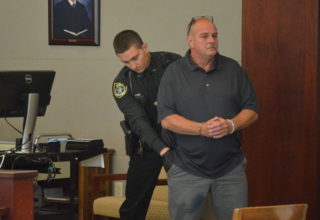 Flagler County Sheriff's bailiff Trevor Jacob searches Jerald Medders moments after sentence was pronounced and he was handcuffed this morning in a courtroom at the Flagler County courthouse. He was sentenced to 15 years in prison, but may be out in 12. (© FlaglerLive)