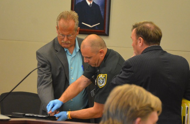 Jim Davis, left, being fingerprinted after his sentencing to a year's probation in circuit court Thursday. His attorney, Doug Williams, is to the right. (© FlaglerLive)