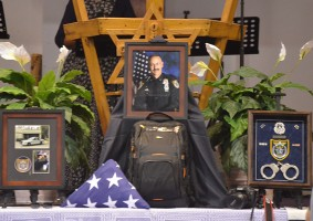 Joe Delarosby's life markers: his service as a deputy, his camera, his backpack. Click on the image for larger view. (© FlaglerLive)