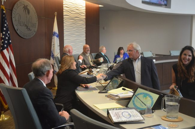 Palm Coast Observer John Walsh, seen here shaking hands with Palm Coast Council member Heidi Shipley in 2015, has had various partnerships with the city over the years and has consistently backed Holland. (© FlaglerLive)
