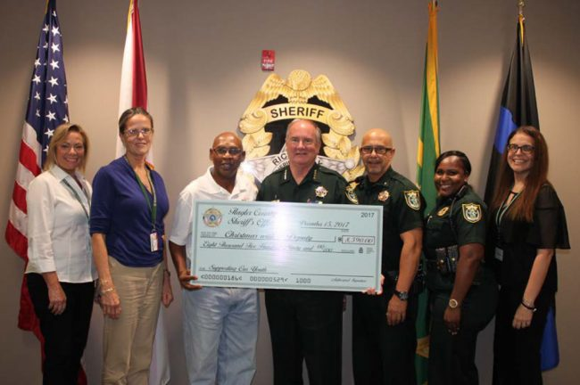Flagler Sheriff's employees have been donating money all year to the charity Larry Jones established in 2008, for a total of $9,000 to be donated for Friday's shopping spree in the form of gift cards to 125 children. From left, Carol Skelton, Kathy Vazquez, Larry Jones, Sheriff Staly, Lou Miceli, Althea Civil, and Mary Dinardi.