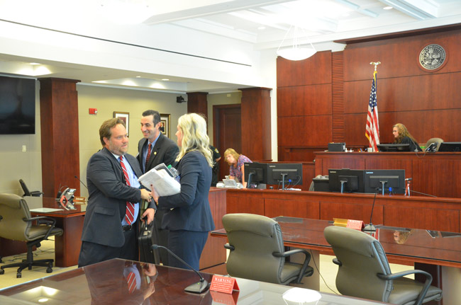 Defense attorney Josh Davis, left, shaking hands with Kayla Hathaway, the sheriff's office's attorney, after the hearing before County Judge Melissa Moore-Stens this afternoon. Assistant State Attorney Jason Lewis is to the right of Davis. (© FlaglerLive)