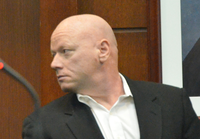 Nathaniel Juratovac looks back at his spouse--a St. Johns County Sheriff;'s deputy--moments after his sentence in a St. Augustine courtroom, and before he was taken into custody. He will serve four years in prison. (c FlaglerLive)