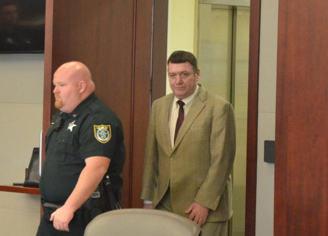 Michael Bowling arriving for trial Monday behind deputy Brian Sheridan. (© FlaglerLive)
