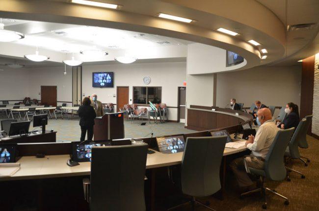 Deputy Clerk Kate Settle adfministers the oath of office to Jon Netts this evening. Former Mayor Netts is now Council member Netts again. (© FlaglerLive)