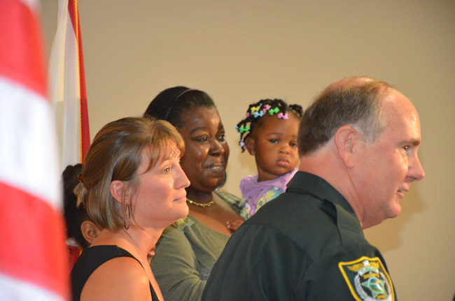 Saviors and survivors: Undersheriff Rick Staly presented Lifesaver Awards to 911 operator Genice Caccavale, in the foreground, and Alicia Fennell, who held her grandchild, Kelisa, to whom she administered CPR as she heard instructions from Caccavale over the phone Saturday, averting a drowning. Leon'ntashia Leggette, 8, who brought Kelisa out of the water, was behind Caccavale. (© FlaglerLive)