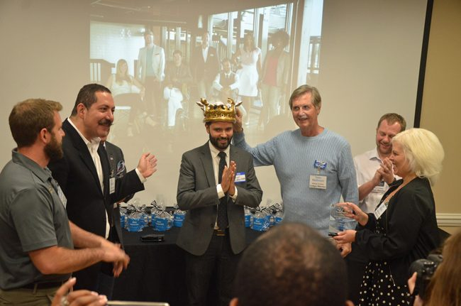 Angel Gonzalez is crowned winner of the 2016 Office Divvy Most Interesting Start-Up Contest for his Snappy Kraken company. He was flanked by Ky Ekinci (right), co-founder of Office Divvy with Lisa Ekinci (right), and judge and mentor (c FlaglerLive)