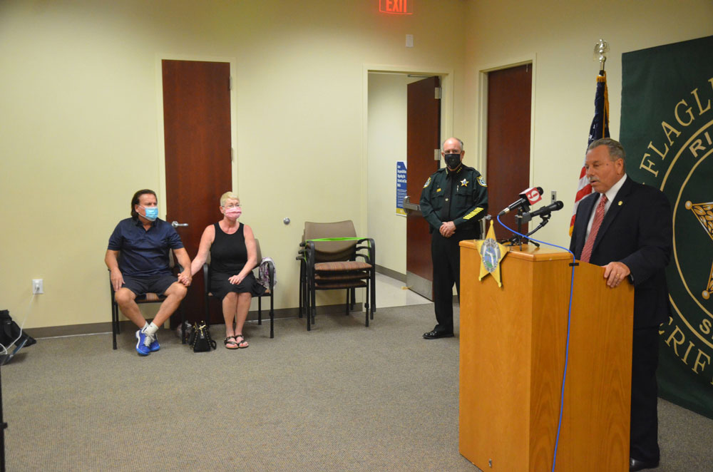 State Attorney R.J. Larizza speaking today, with Sheriff Staly and Renee and Chip DeAngelis in the room. (© FlaglerLive)