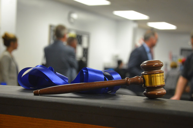 The judge's gavel in the mock courtroom built by Matanzas's construction flagship students for its law and justice flagship program, inaugurated Wednesday. The figures in the background are Superintendent Jim Tager and Matanzas Principal Jeff Reaves. (© FlaglerLive)